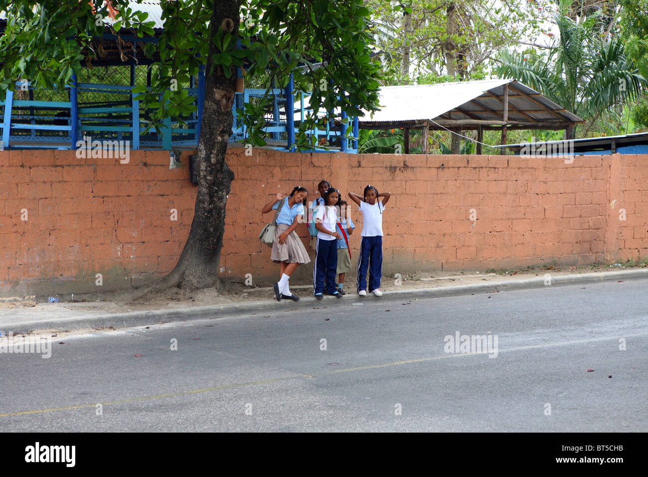 Group on young Dominican school children all dressed in uniform waiting outside their school - Stock Image