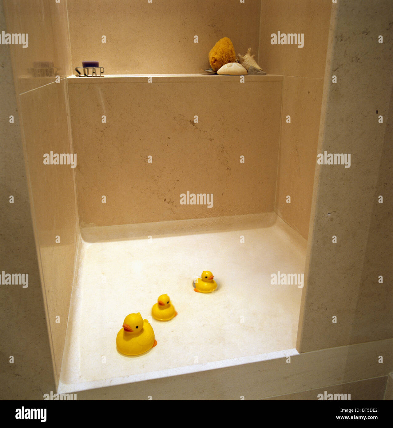 Close-up of yellow plastic ducks on floor of shower in modern white ...