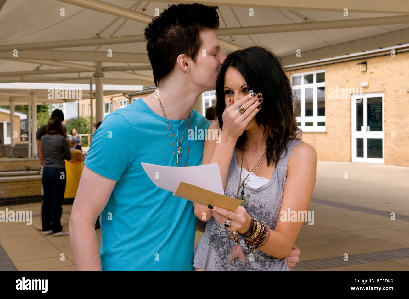 Happy teenagers outside school after receiving exam results - Stock Image