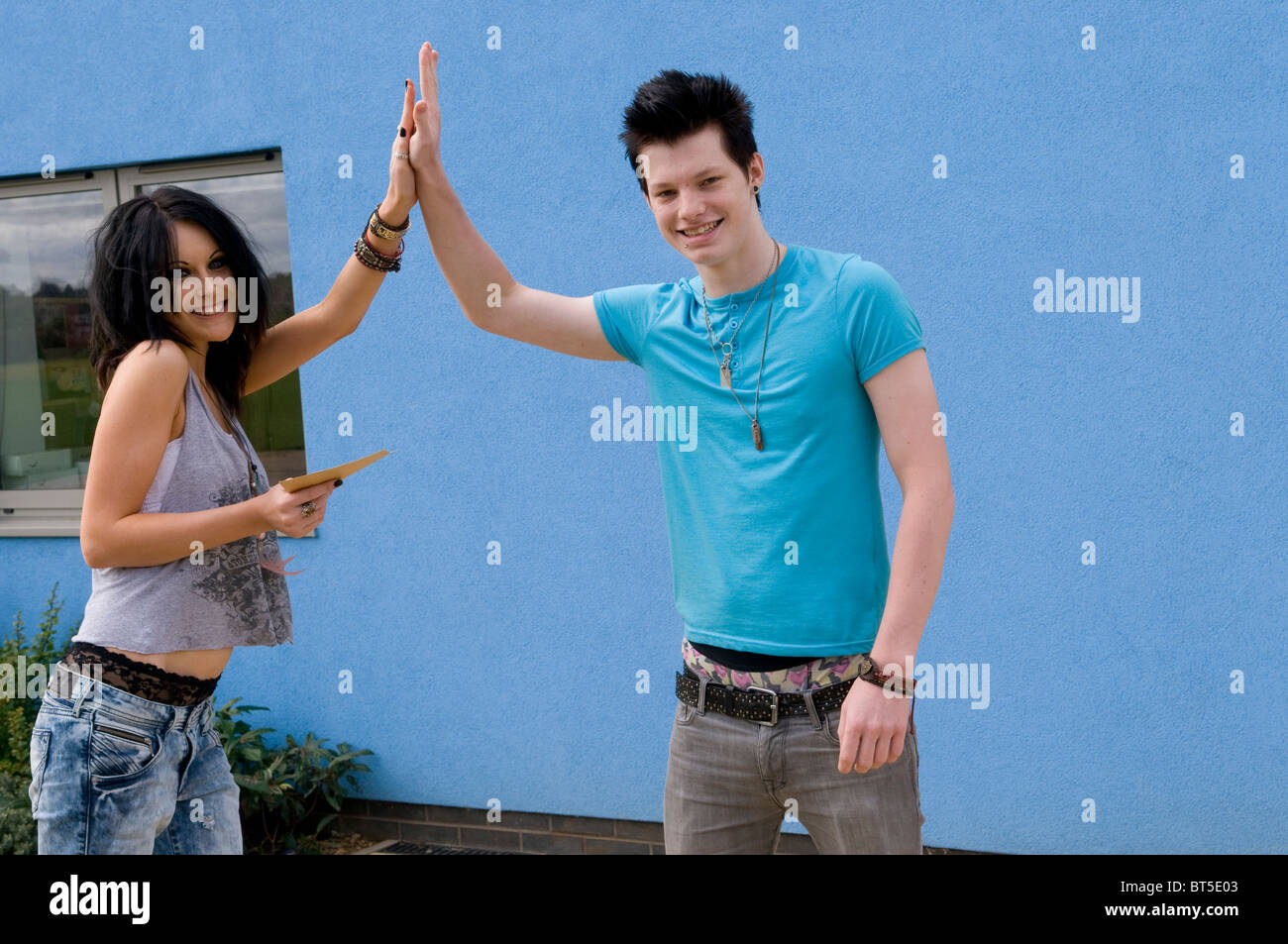 Happy teenagers outside school doing a high five after opening exam results - Stock Image