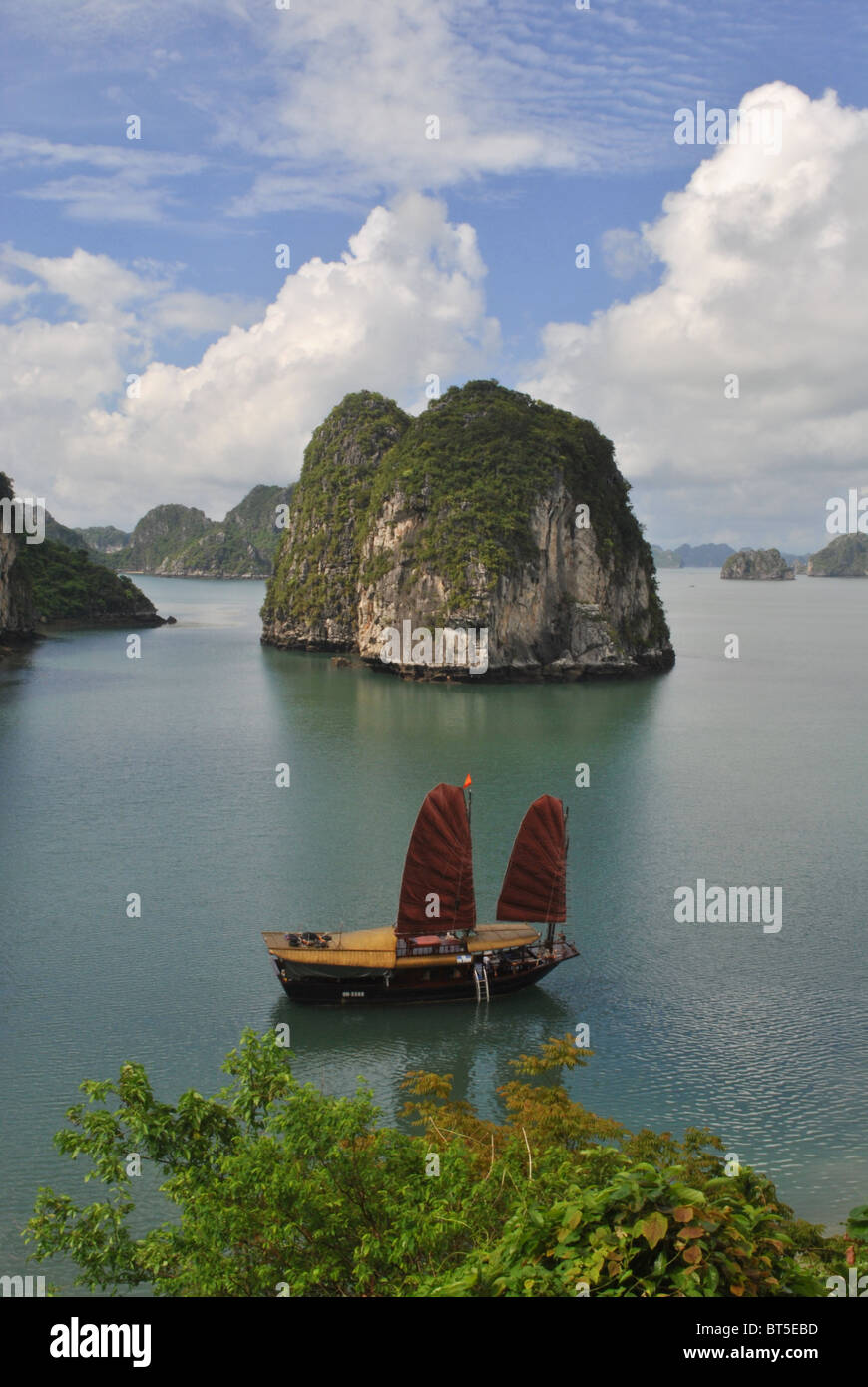 Junk with red sail in Halong Bay, Vietnam - Stock Image