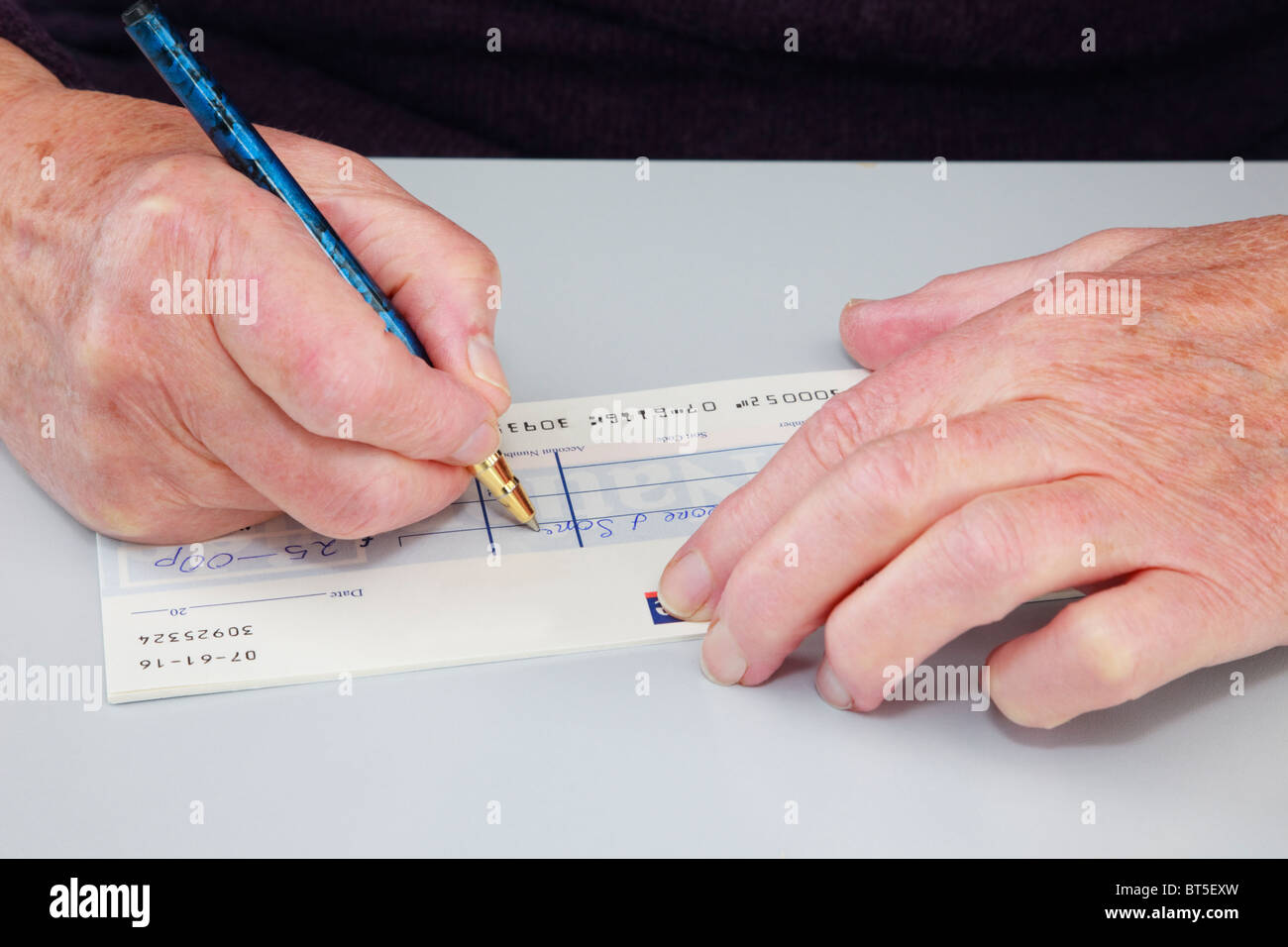 Close-up of a senior elderly woman pensioner writing a cheque (check) to pay a bill. England, UK, Britain. - Stock Image