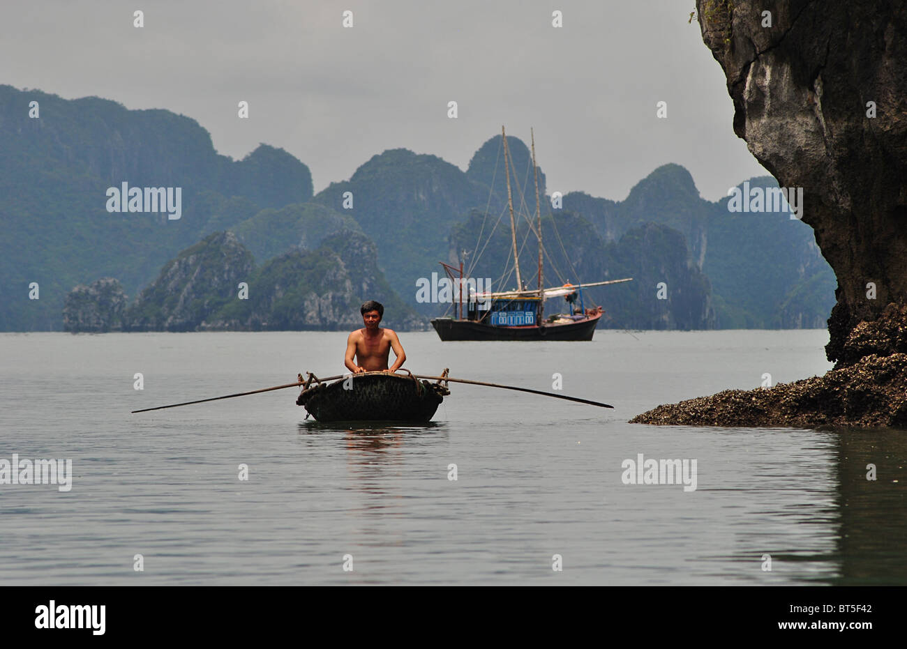 Junk and rowing boat in Halong Bay, Vietnam - Stock Image