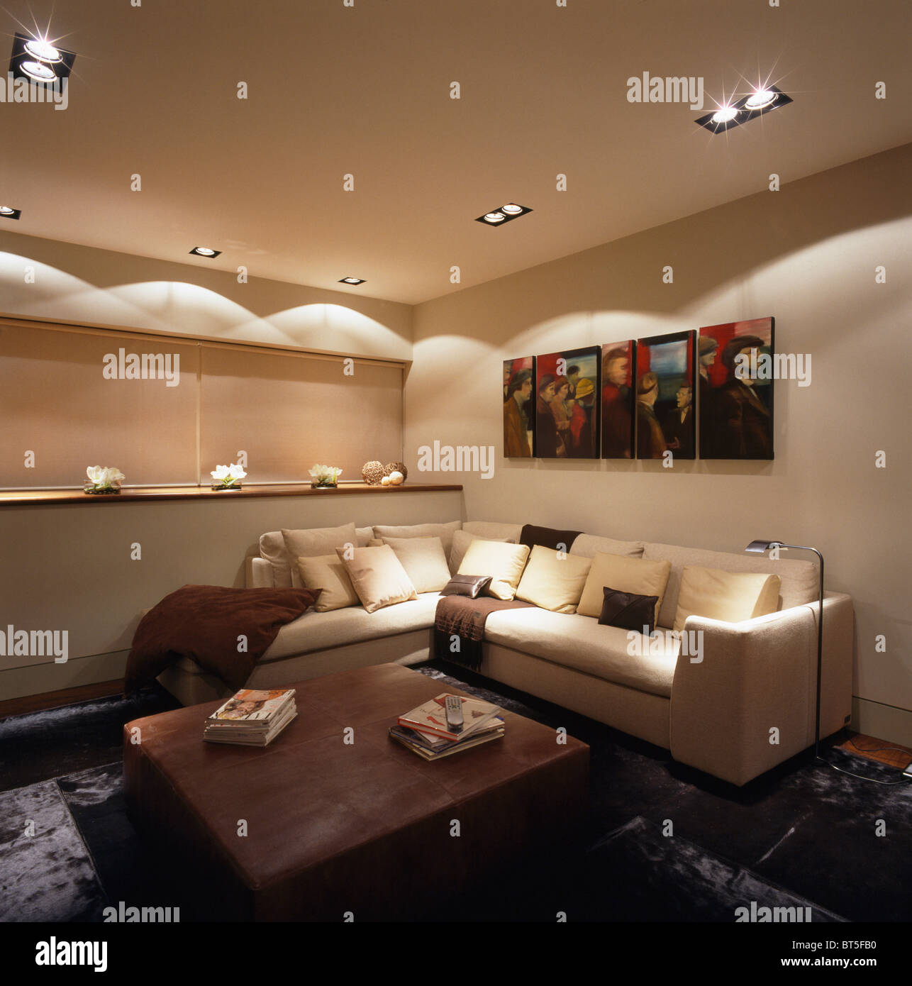Recessed and ceiling lighting above L-shaped sofa in modern apartment townhouse living room - Stock Image