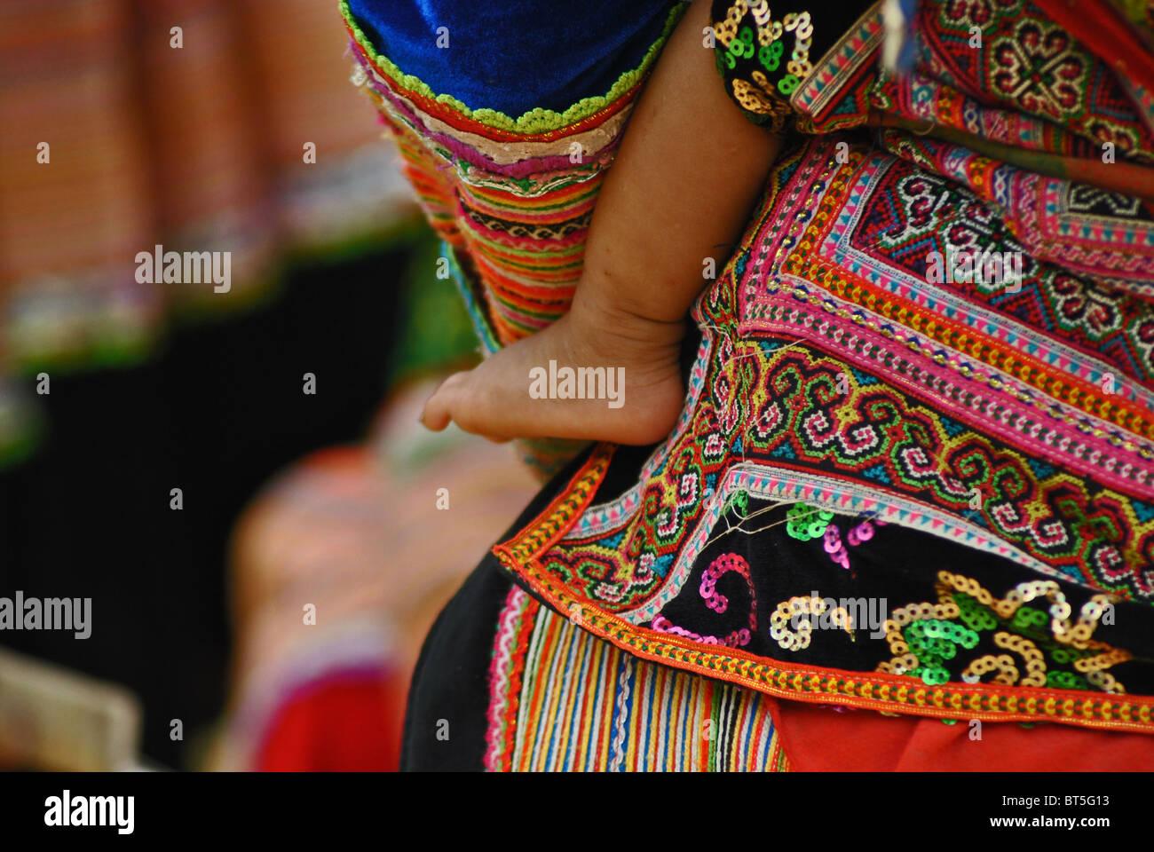 Flower Hmong baby on mother's back near Sapa, Vietnam - Stock Image