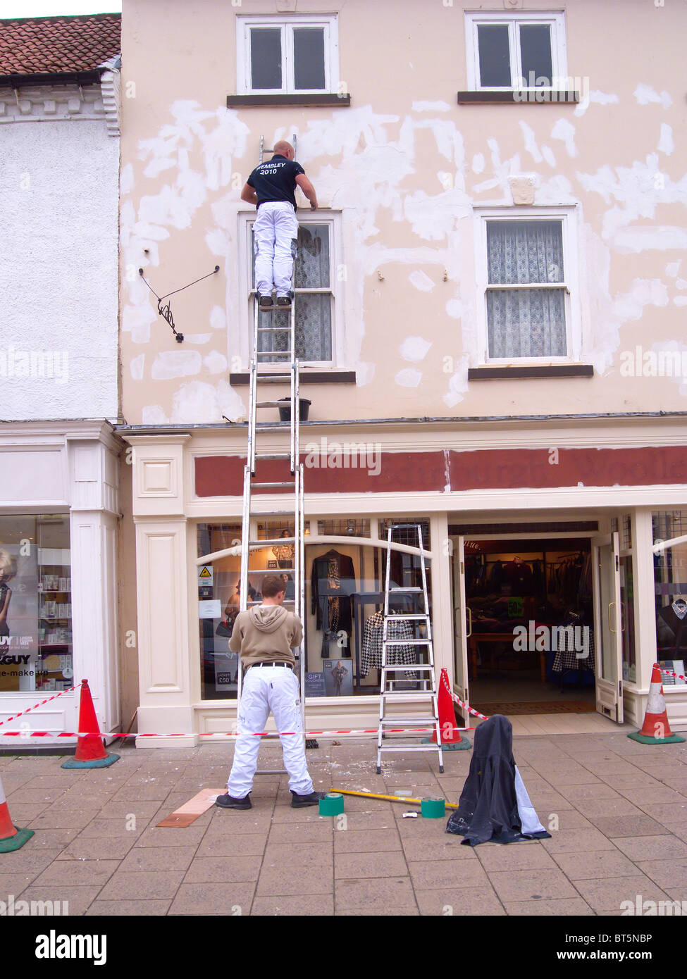 Decorators painting the exterior of a shop in Northallerton North Yorkshire - Stock Image
