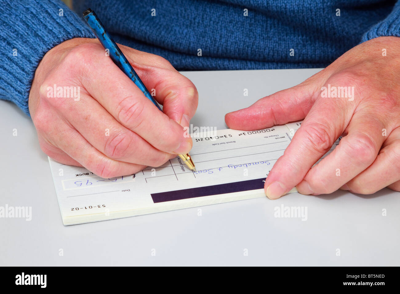 Close-up of a mature woman writing a cheque (check) in a cheque book to pay a bill. England, UK, Britain. - Stock Image