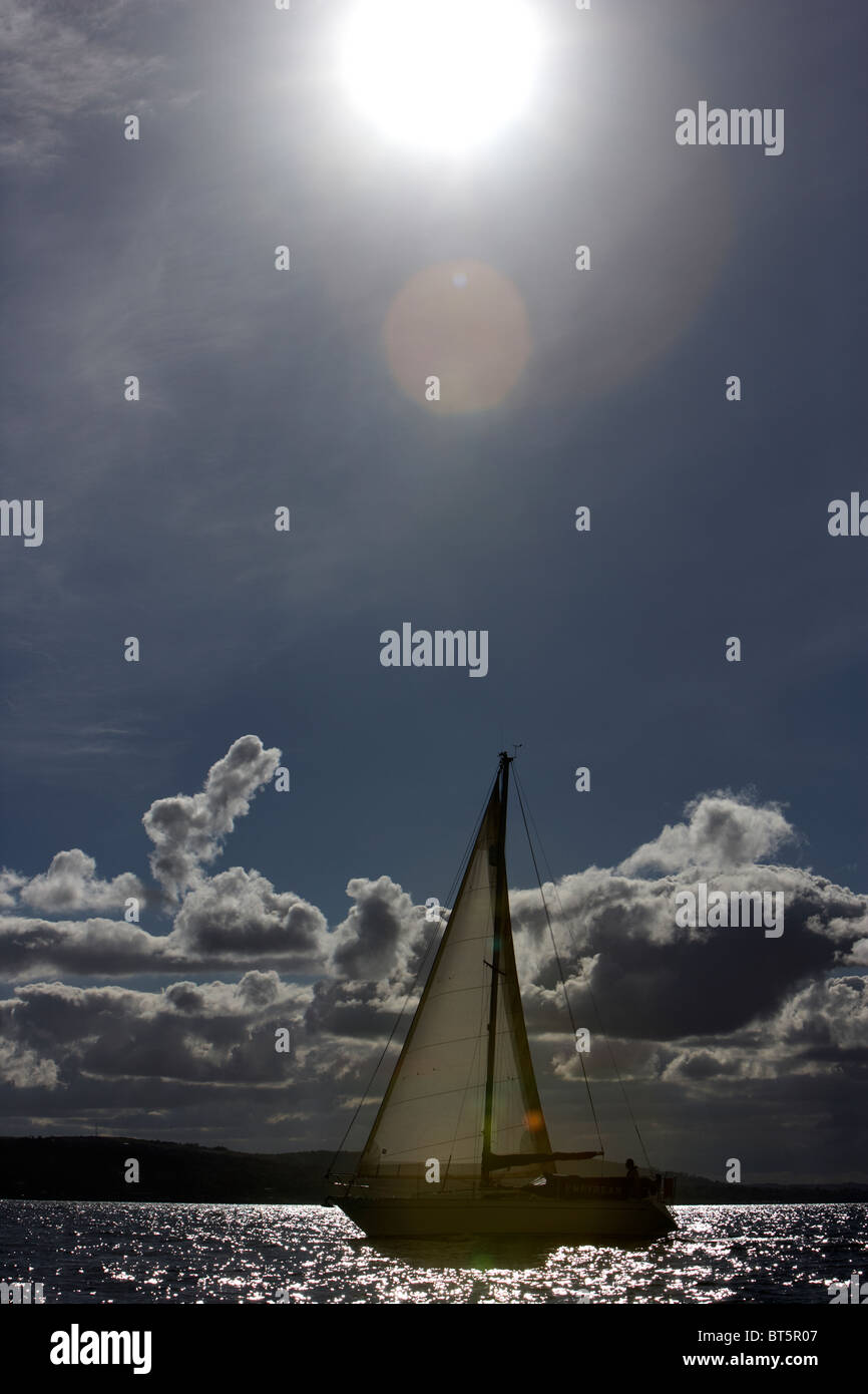 sun shining down on yacht under sail across belfast lough northern ireland uk with lens flare - Stock Image