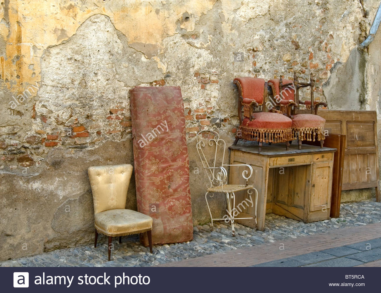 Antique furniture left behind in a backyard of the old town of Albenga, Liguria, North West Italy. - Stock Image