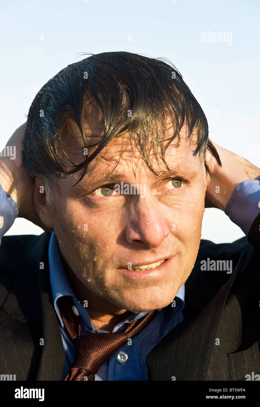 A depressed and anxious looking businessman who is soaking wet. - Stock Image