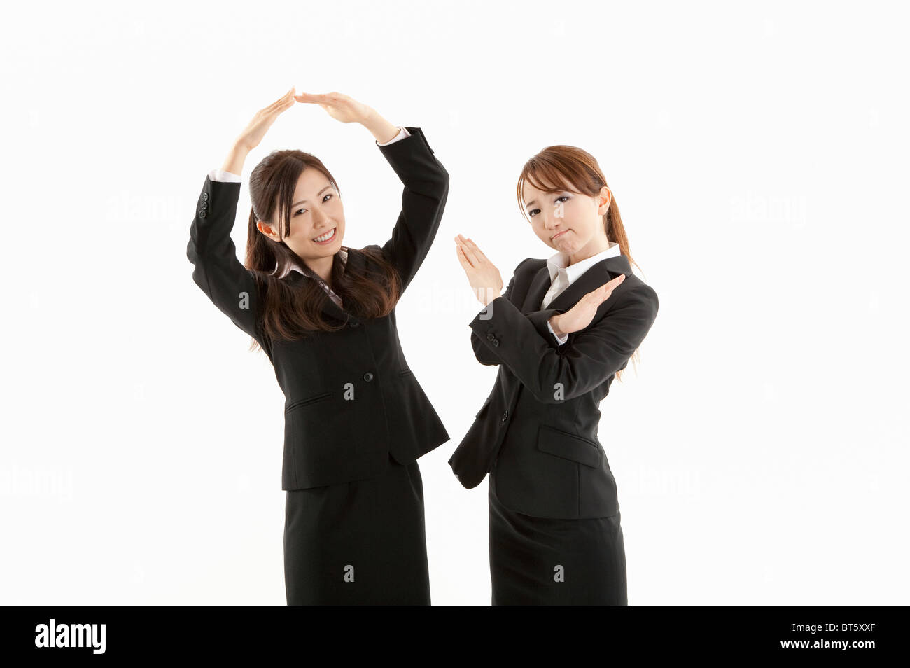 Two businesswomen making circle and cross shape with hands - Stock Image