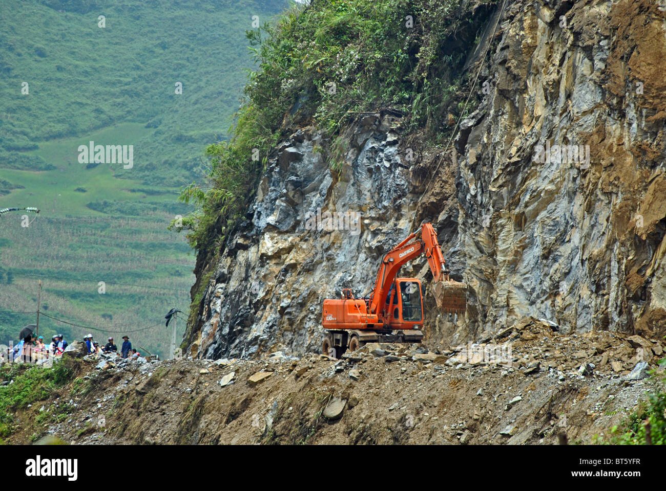 A digger clears rubble from a blocked road after landslides and rockfalls triggered by heavy rain in Sapa, Vietnam - Stock Image