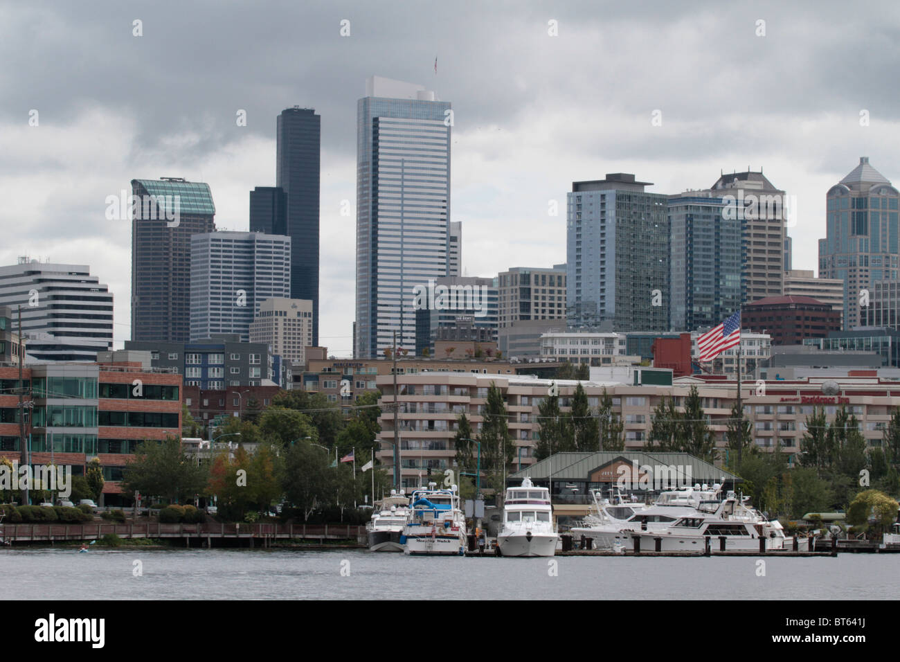 cloudy Seattle skyline from South Lake Union with boats docks and an American flag in view - Stock Image