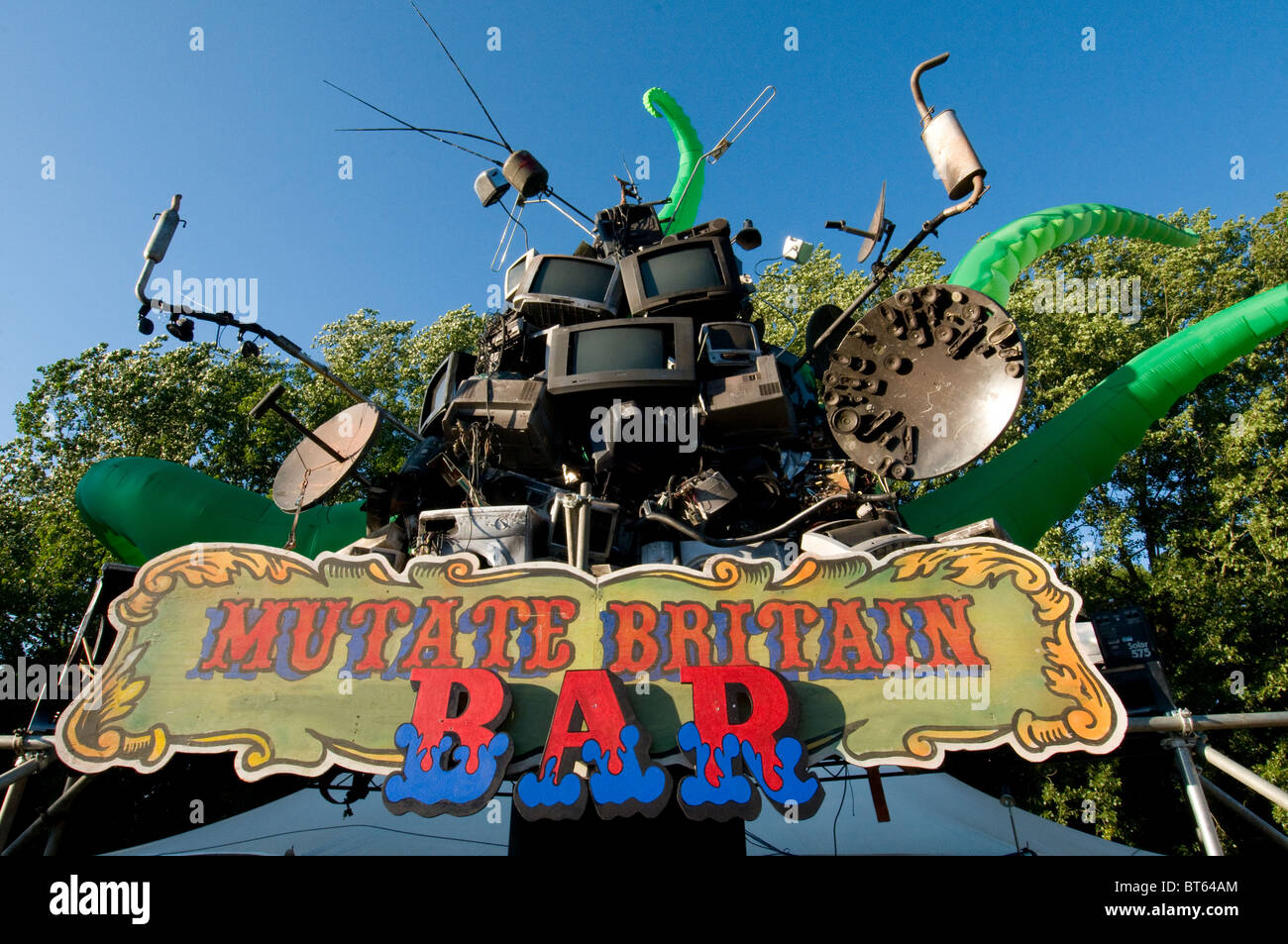 2010 Glastonbury Festival of Contemporary Performing Arts festival mutate britain bar front sign scrap tv satellite - Stock Image