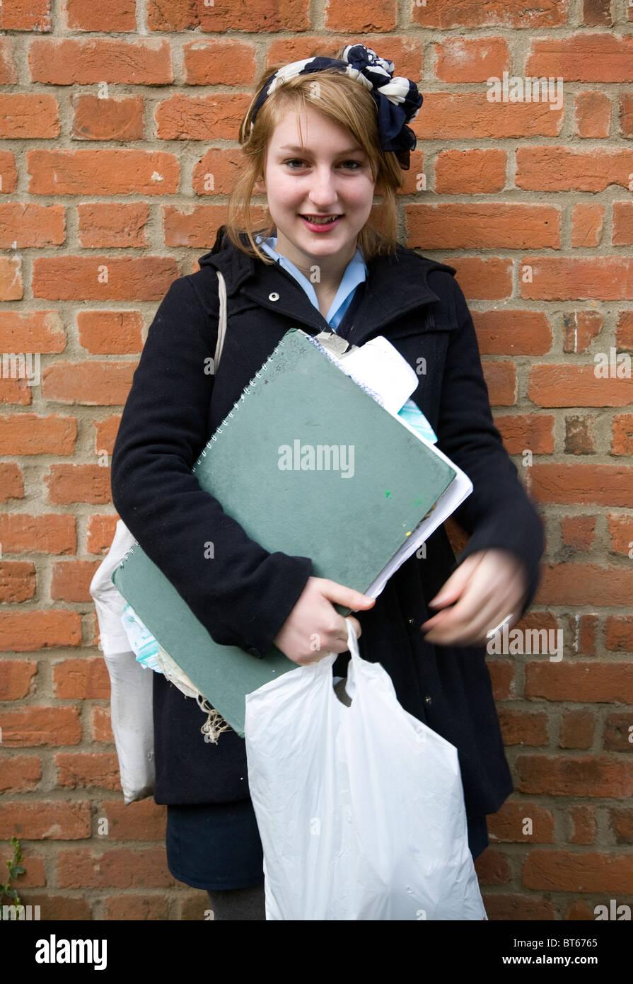 Teenage school girl holding art folder wears coat - Stock Image
