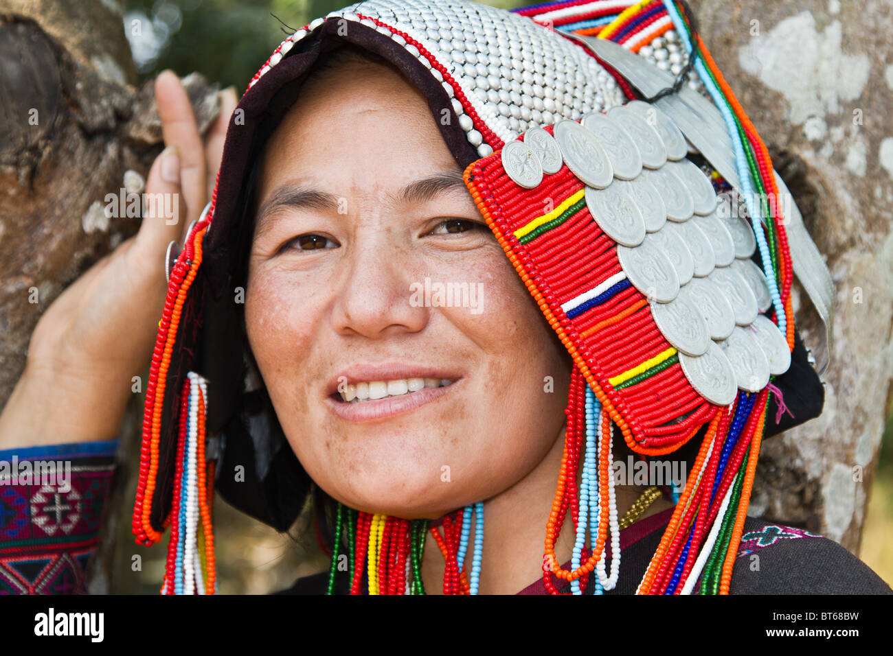Close up of an Akha woman wearing a traditional headdress made of silver balls and coins - Stock Image