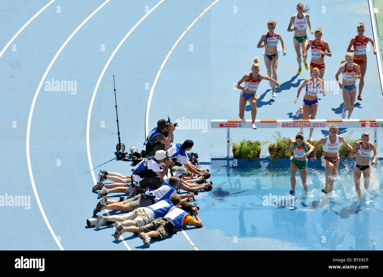 photographers get low position to capture the participants of a female 3000m steeplechase jumping over water obstacle Stock Photo