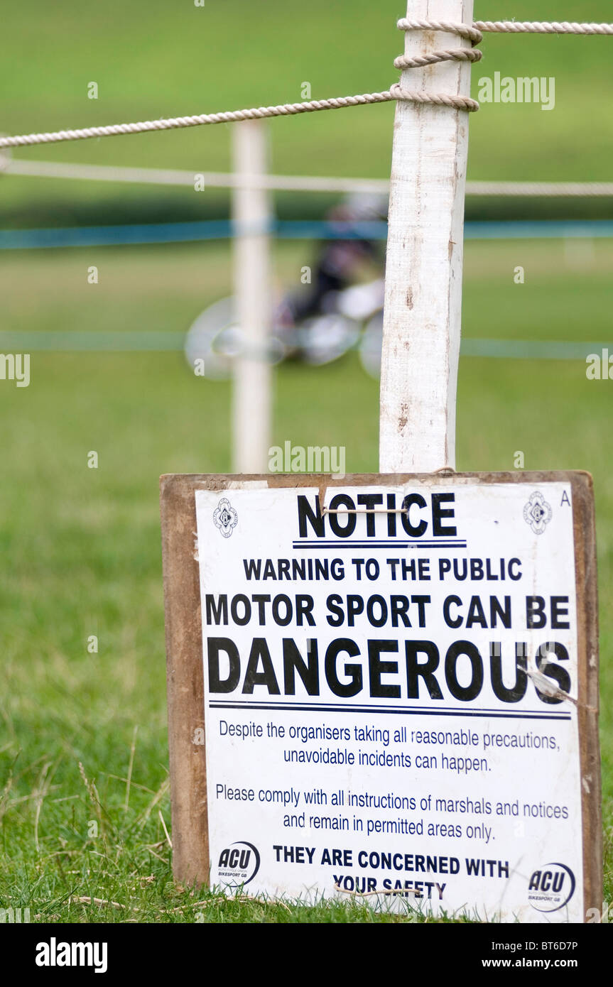 public indemnity liability motorsport motorsports disclaimer dangerous health and safety warning sign insurance - Stock Image