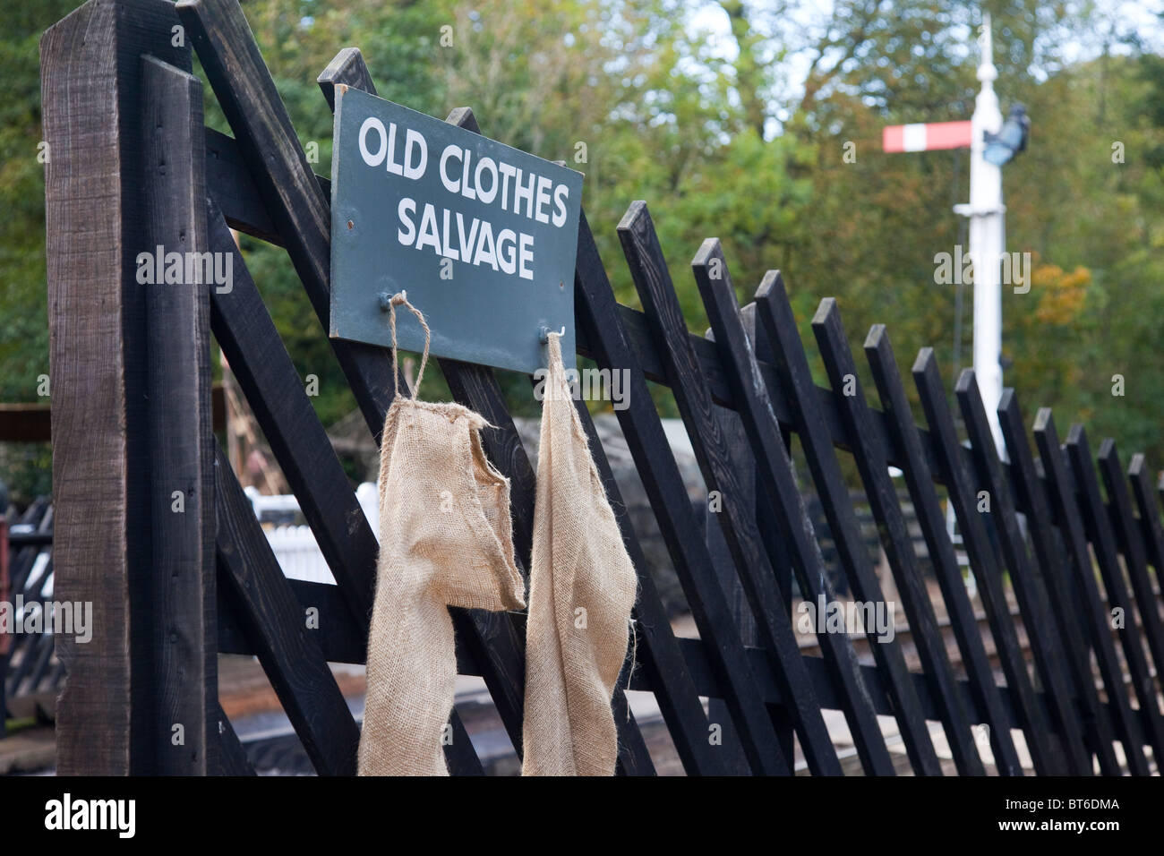 Collection Point for Old Clothes, reuse, recycle, recycling, Salvage and old clothes bags hung on wooden fence in - Stock Image