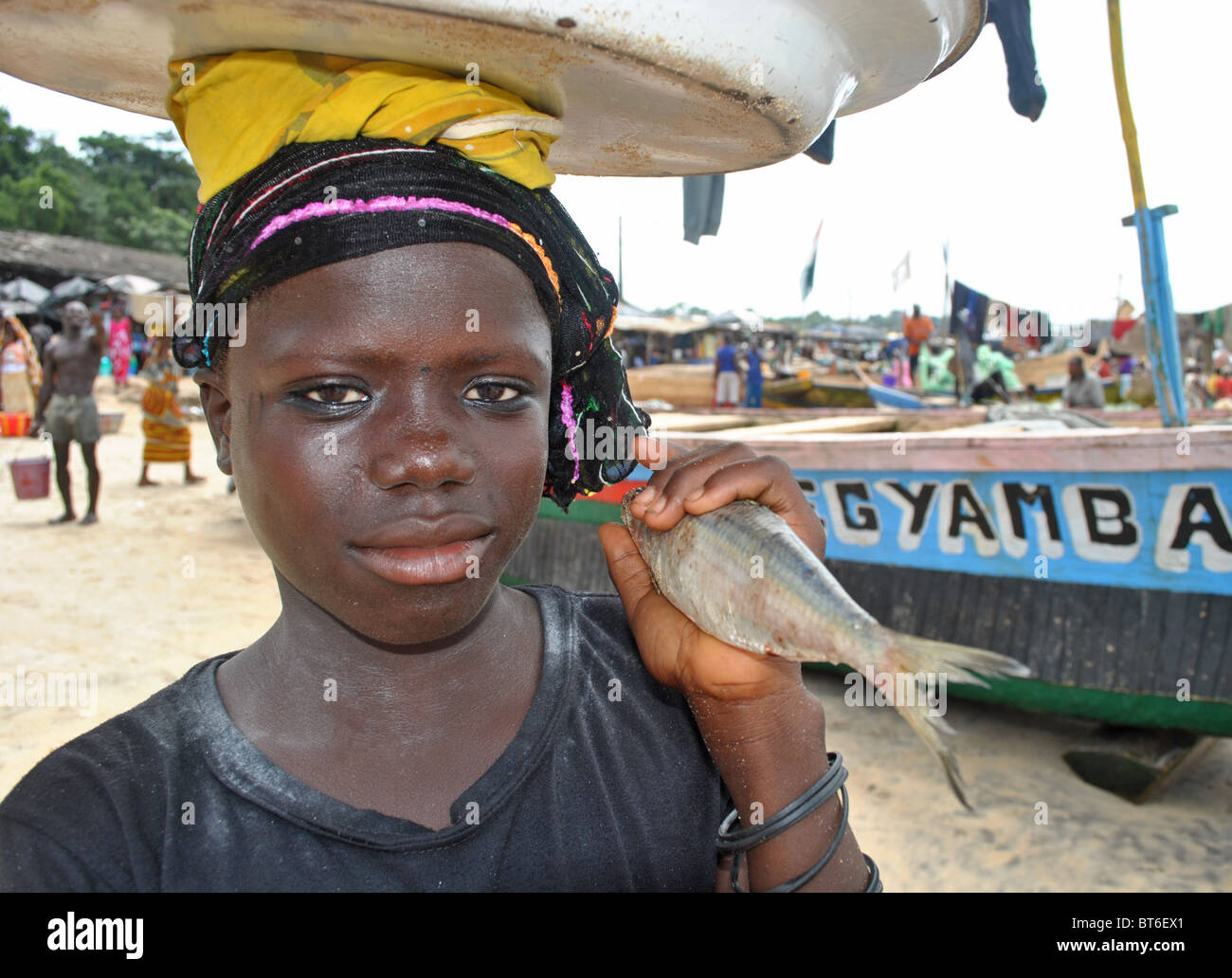 Girl with fish and bucket on a beach in Sassandra, Ivory Coast, West Africa - Stock Image