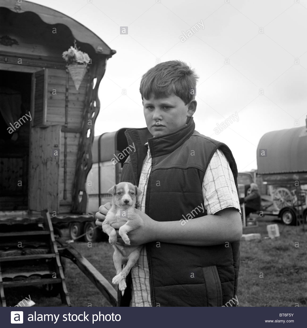 Young lad with a puppy at the Stow-on-the-Wold horse fair, Gloucestershire, UK. - Stock Image