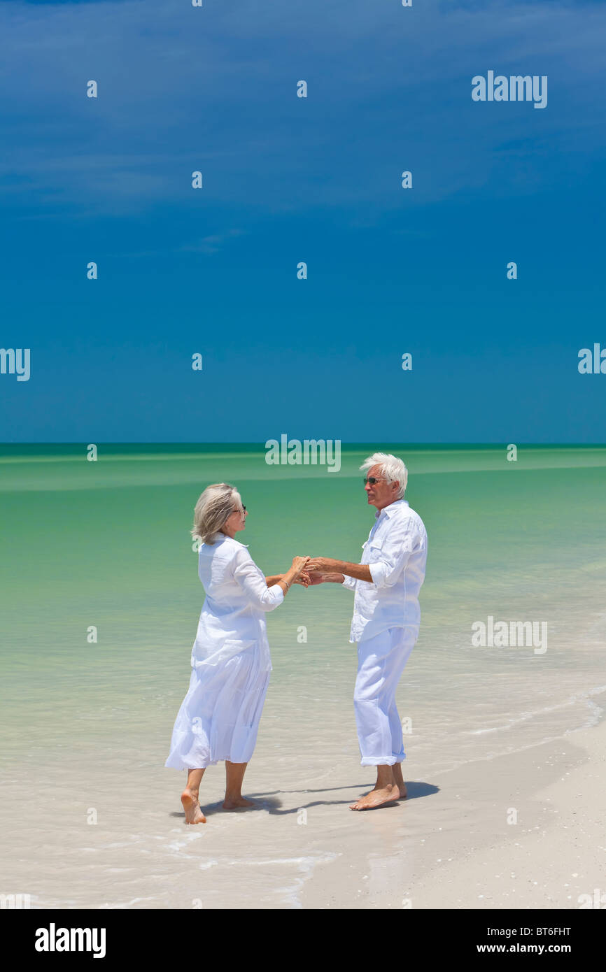 Happy senior man and woman couple dancing and holding hands on a deserted tropical beach with bright clear blue - Stock Image