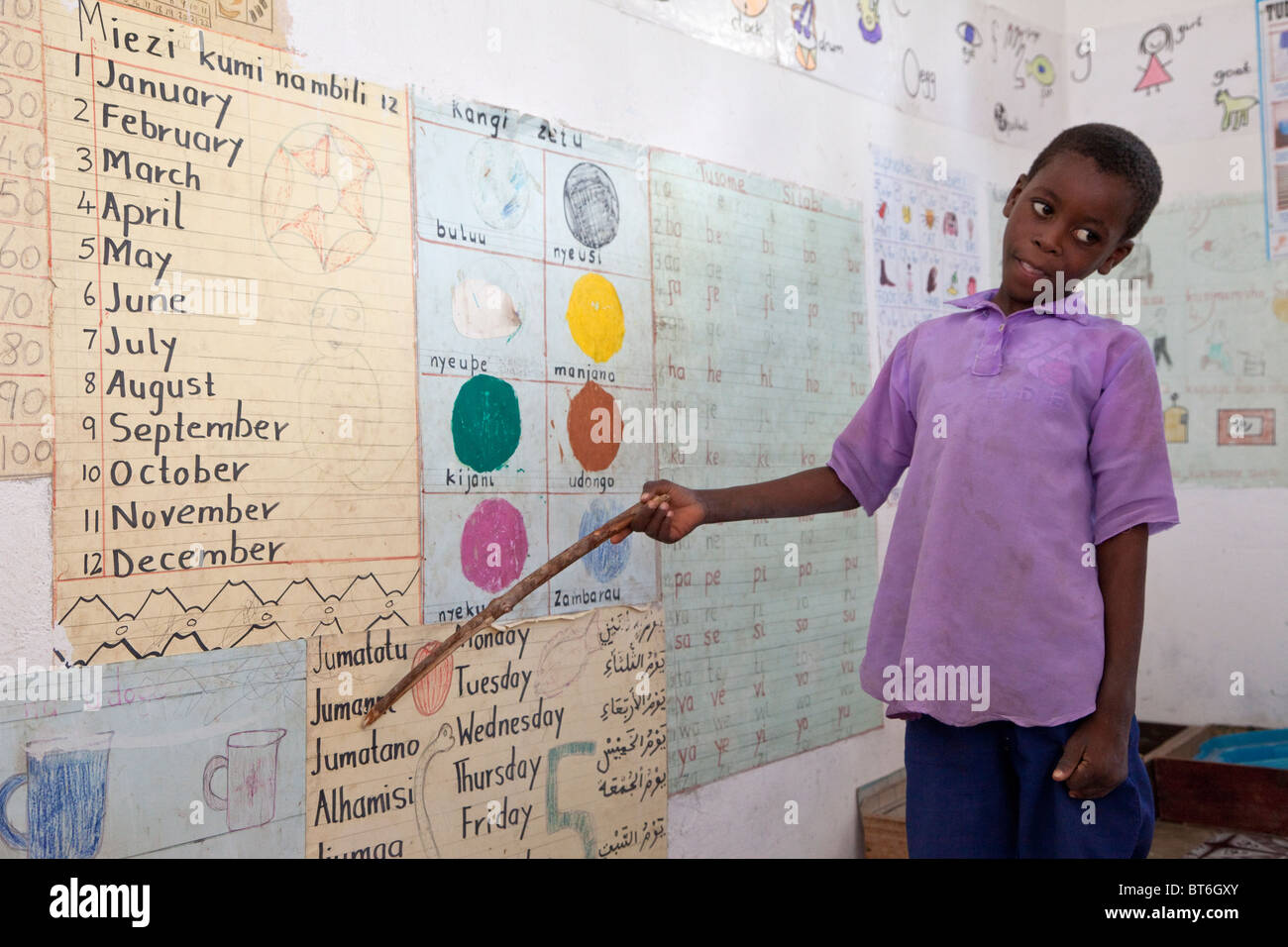 Jambiani, Zanzibar, Tanzania. Young Student Points to the Names of the Days of the Week in Swahili. - Stock Image