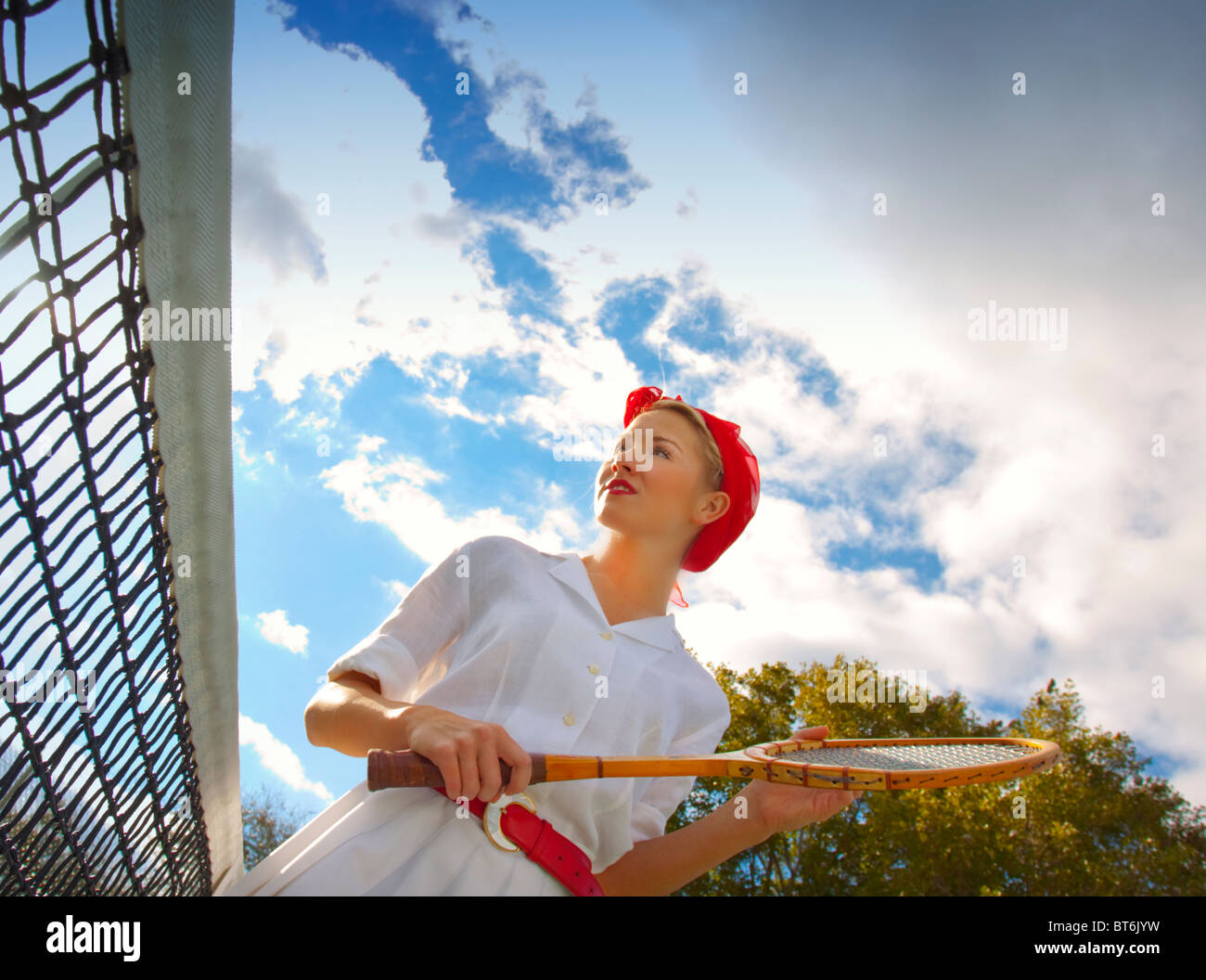 Woman playing tennis on a sunny day - Stock Image