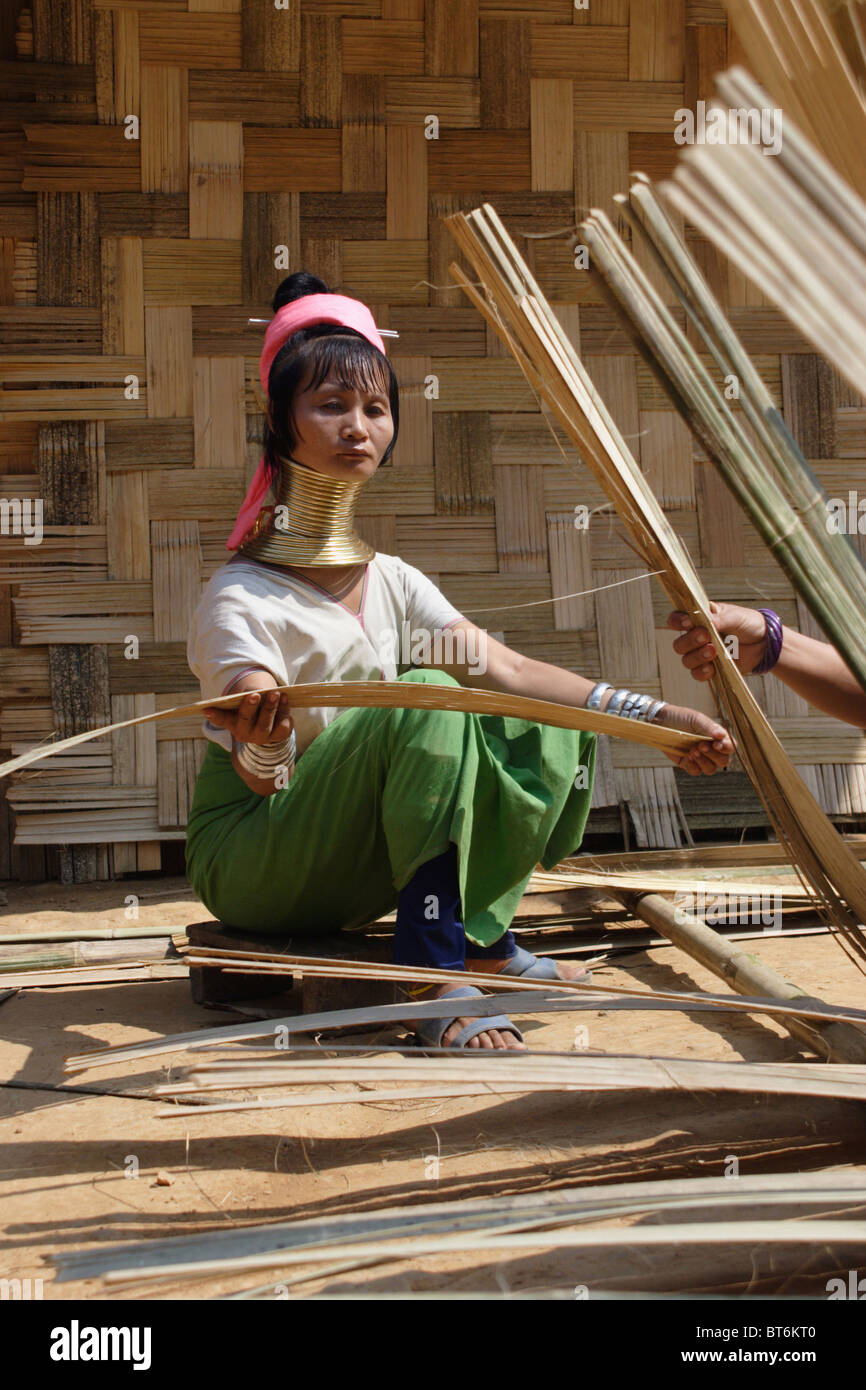 Karen Paduang longneck refugees from Burma (Myanmar) are making a thatched roof in Ban Nai Soi, Thailand. Stock Photo
