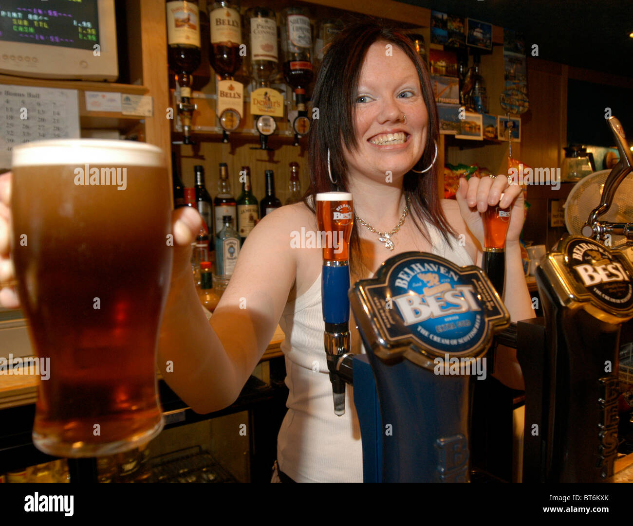 Young barmaid hands over a pint of beer in a UK pub - Stock Image