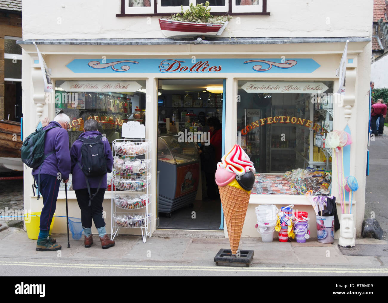 Mature couple in walking gear outside Dollies sweet shop in Robin Hoods Bay, North Yorkshire - Stock Image