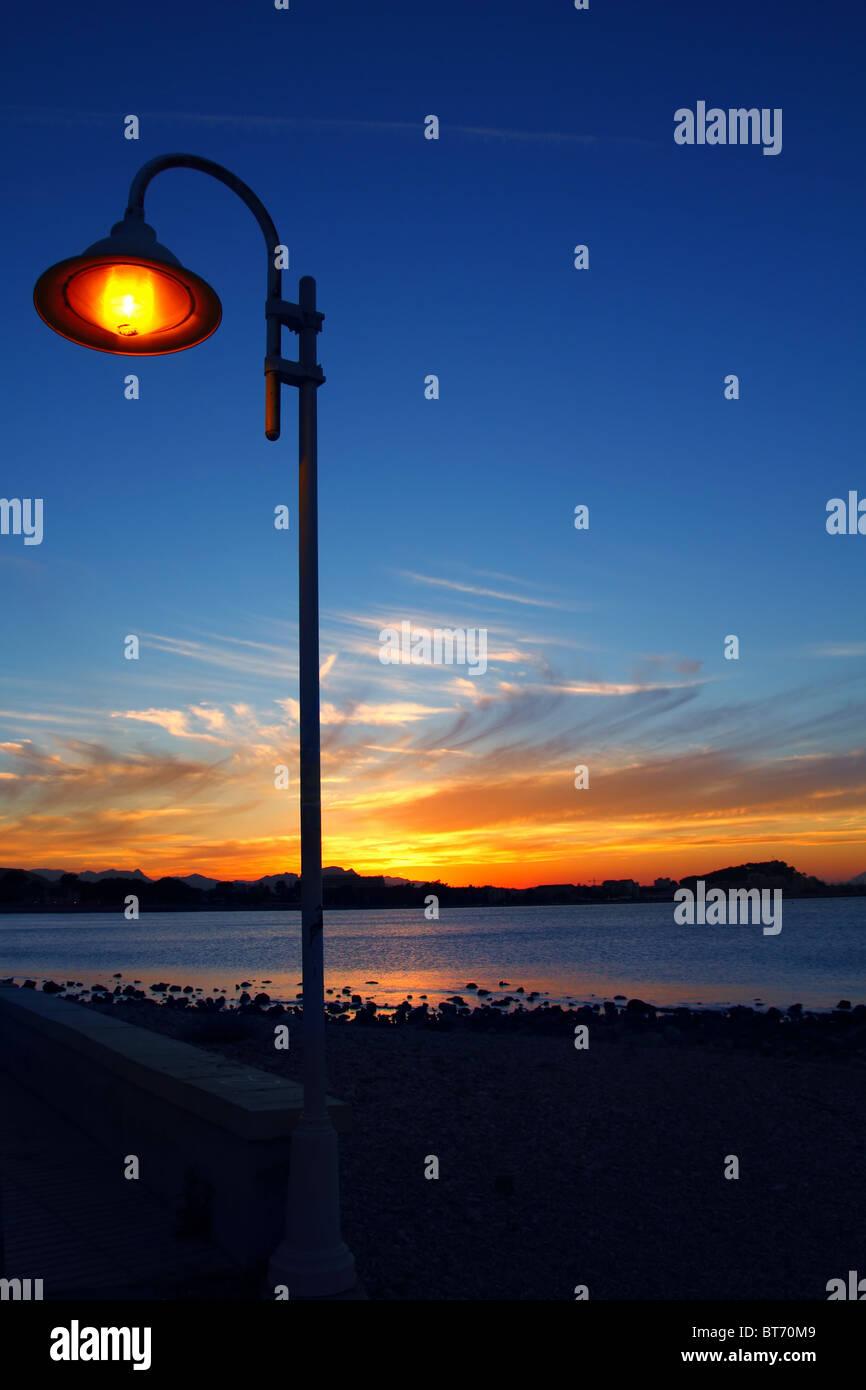 Sunset orange blue seascape light lamppost Mediterranean Denia alicante spain - Stock Image