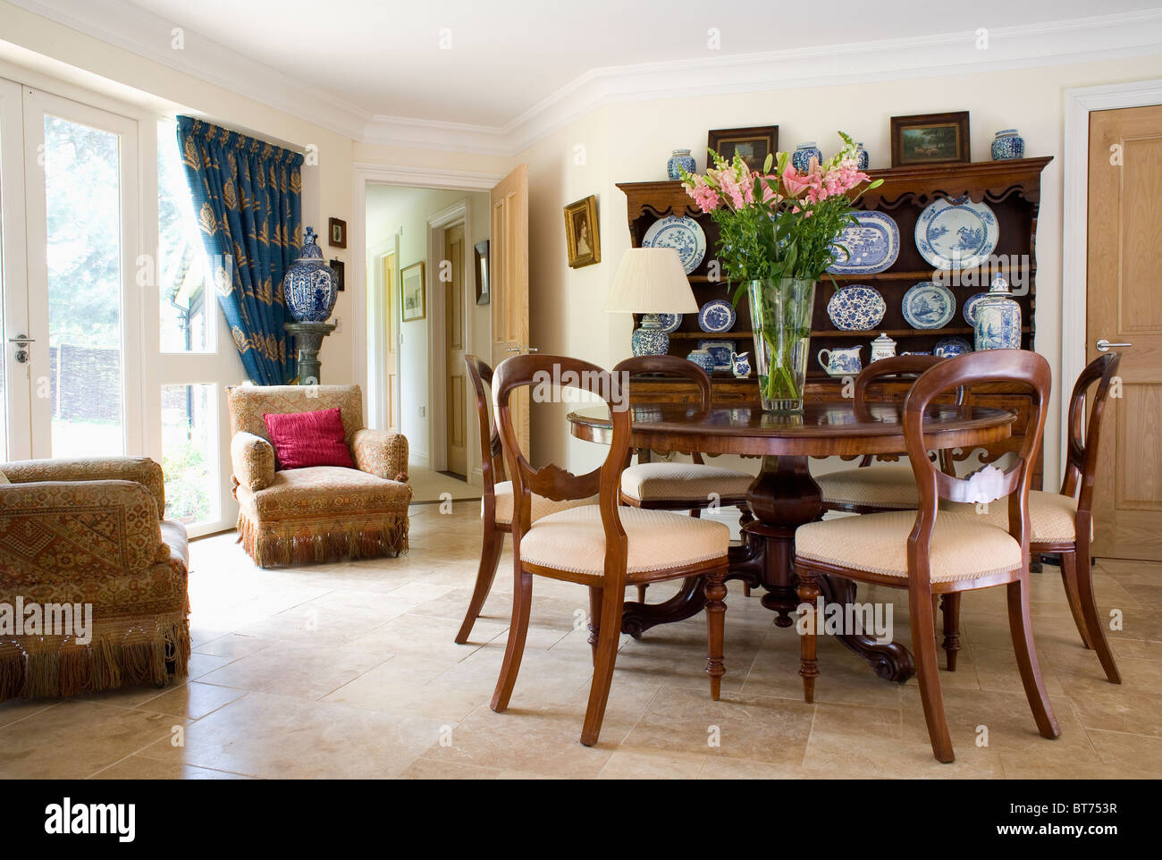 Antique circular table with antique balloon-back chairs in country dining  room extension with limestone flooring - Antique Circular Table With Antique Balloon-back Chairs In Country