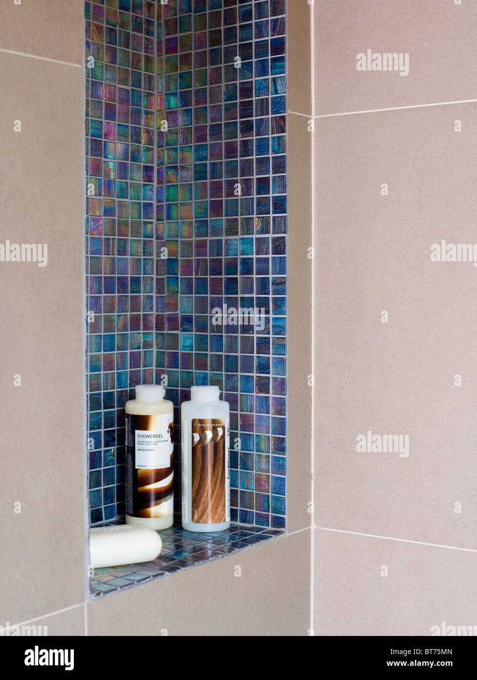 Close-up of bottles of bathroom toiletries in blue mosaic tiled ...