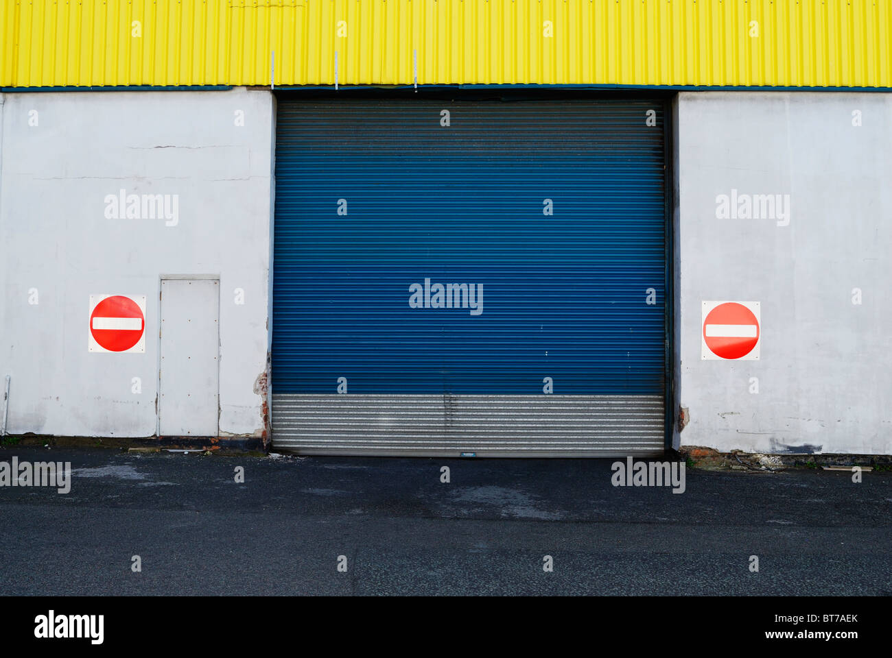 Blue roller shutter doors and no entry signs - Stock Image