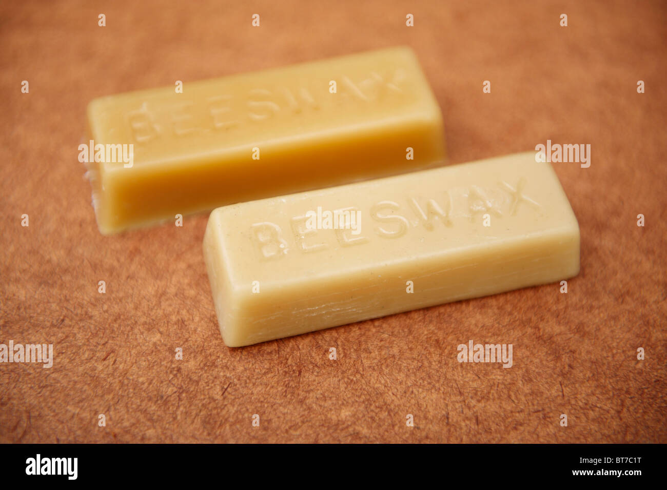 2 blocks of beeswax on a piece of wood - Stock Image