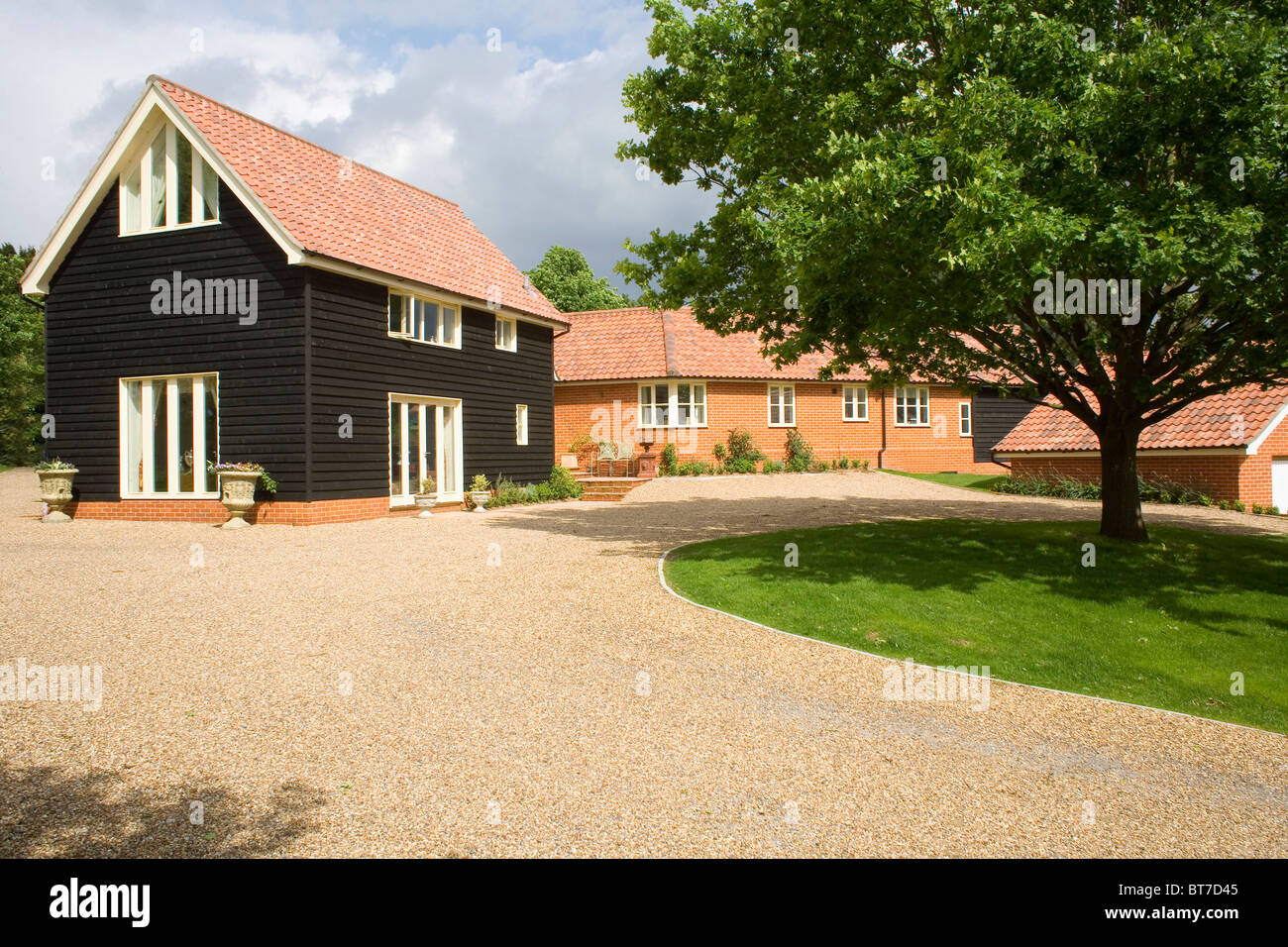 Gravel drive in front of small traditional new build barn for New build barn style house