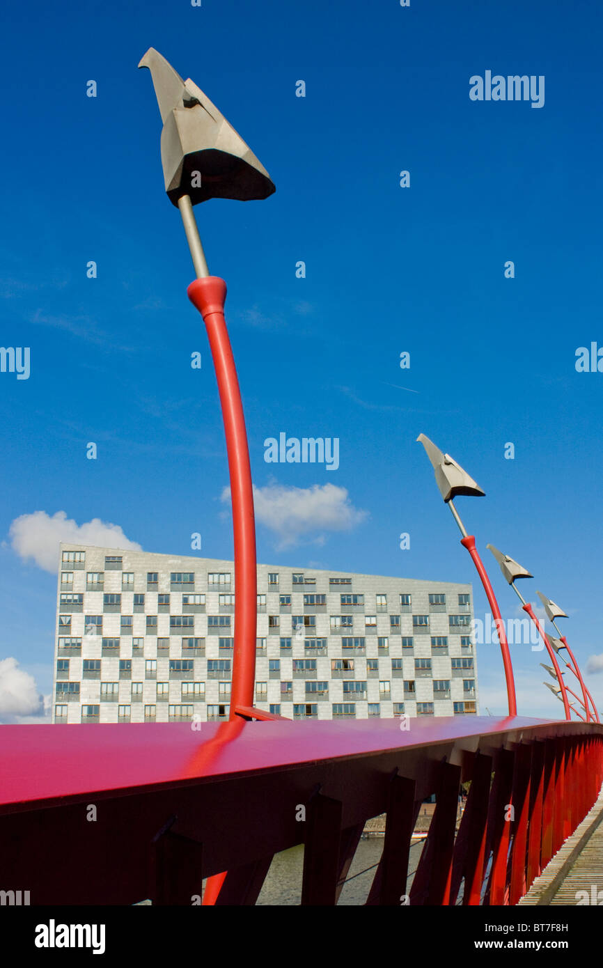 Modern architecture. Red steel bridge in  Amsterdam Eastern Docklands, Sfinx building in background, by  Frits van Stock Photo