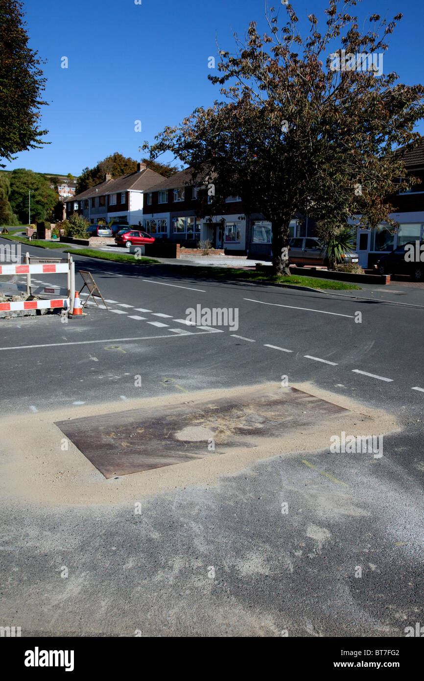 A badly placed metal cover on a road junction can be very hazardous especially for those on two wheels in wet conditions. - Stock Image