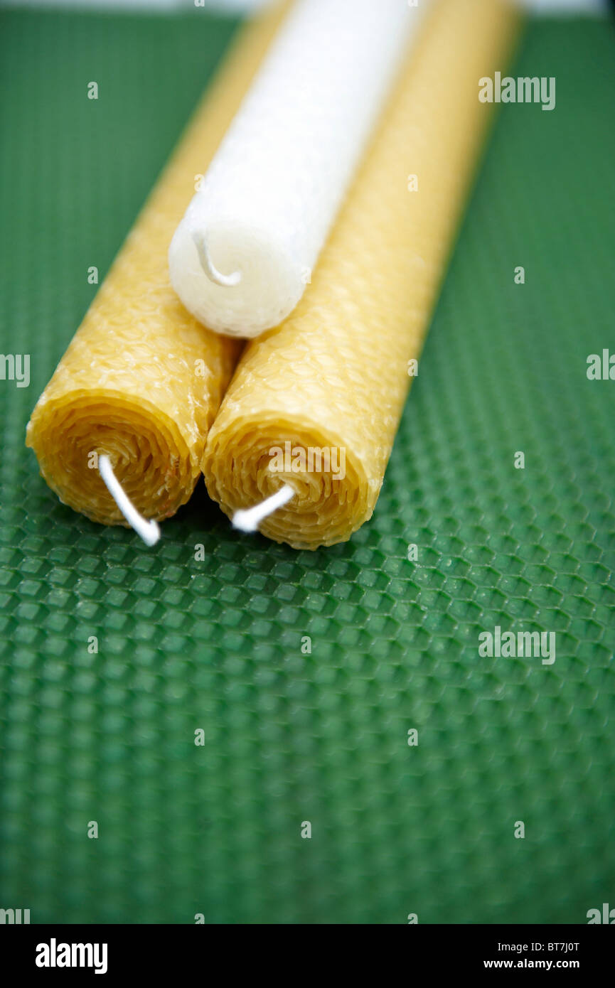 3 wax hand rolled candles, made from sheets of wax, displayed on sheet of wax - Stock Image