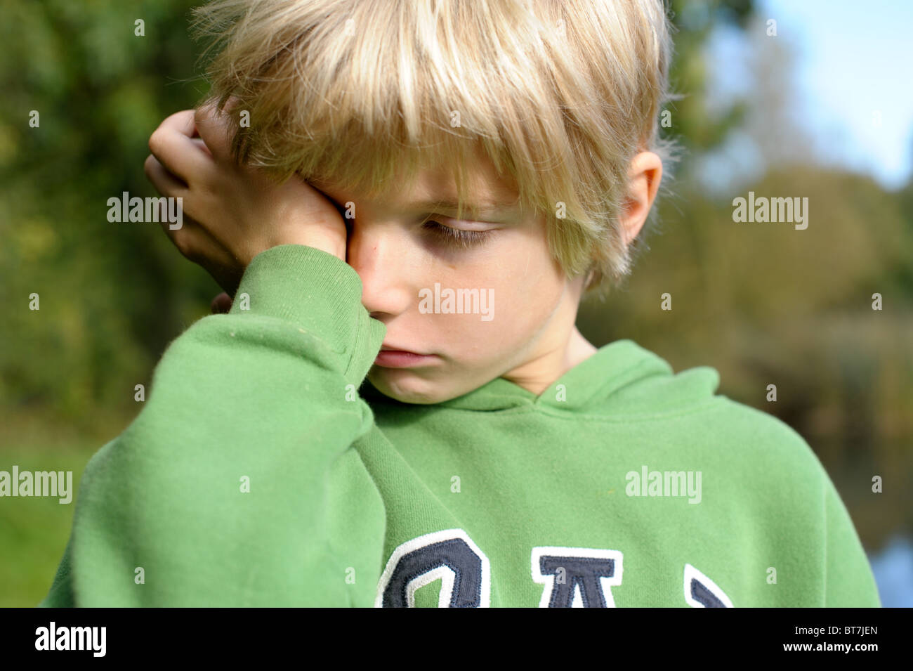 Tearful, sulking, fed-up blond-haired little boy in a green top standing outside - Stock Image