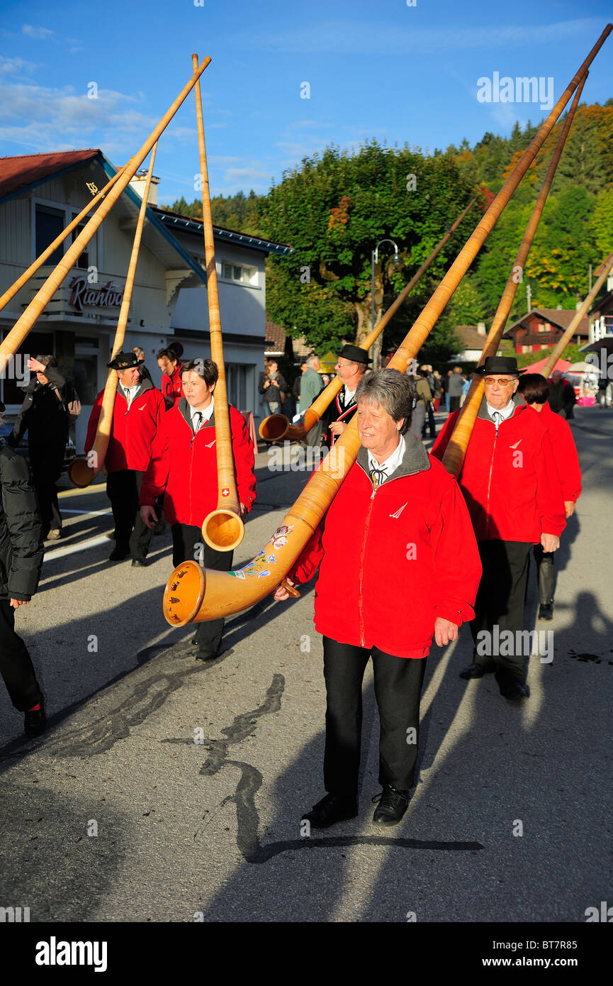 A group of Swiss alphorn players walking down the road in the early morning light with their instruments over their - Stock Image