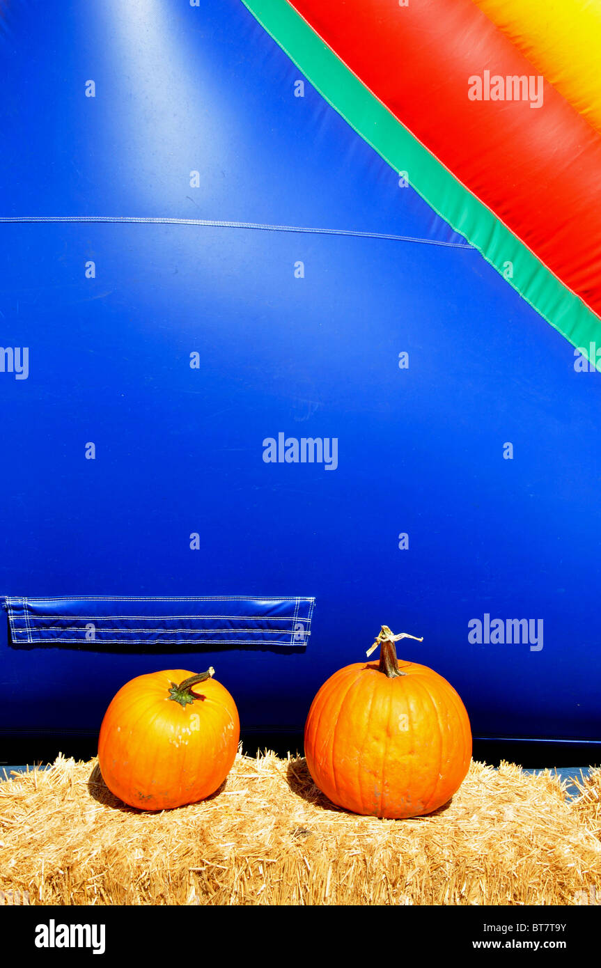 Pumpkins on hay bales in front of an inflatable jumper - Stock Image
