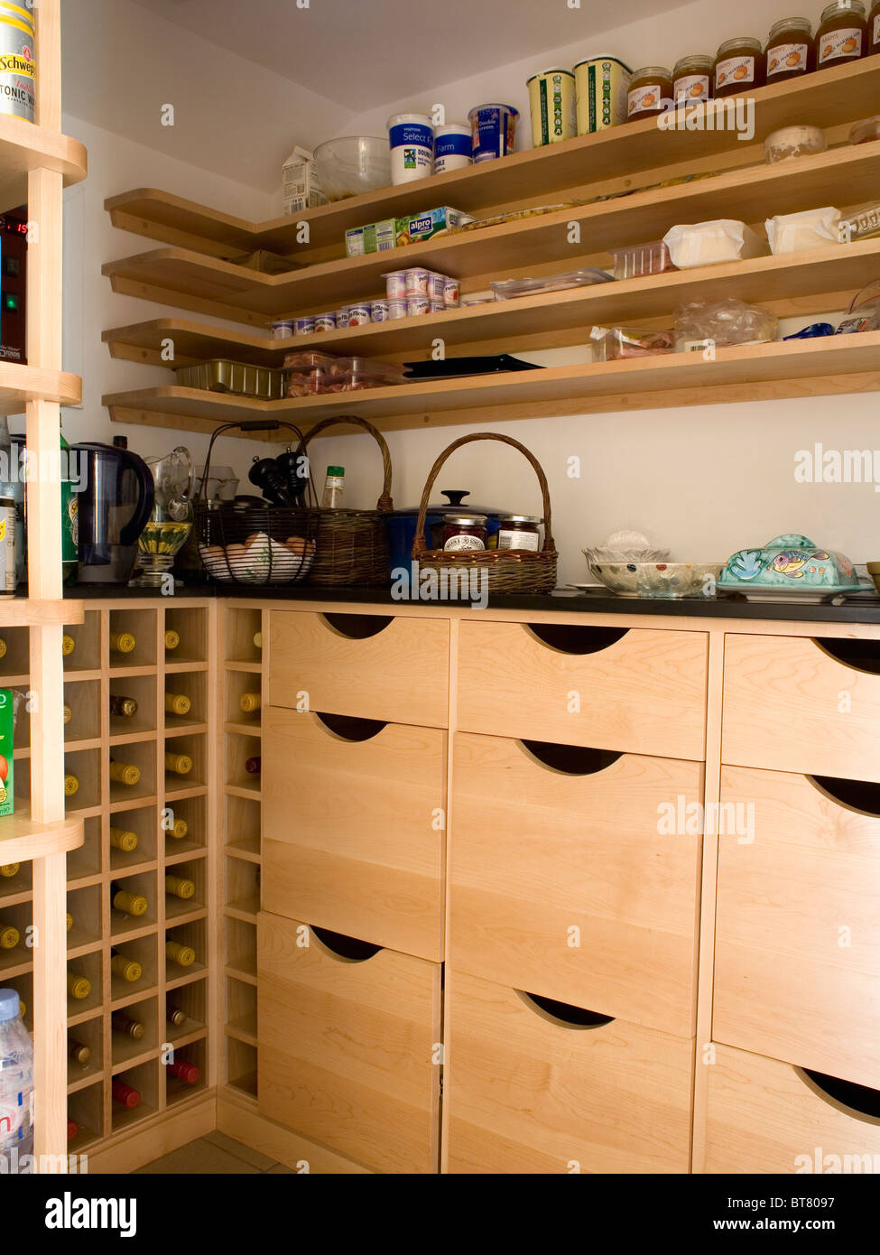 Simple wooden shelving above pale wood storage drawers in corner ...