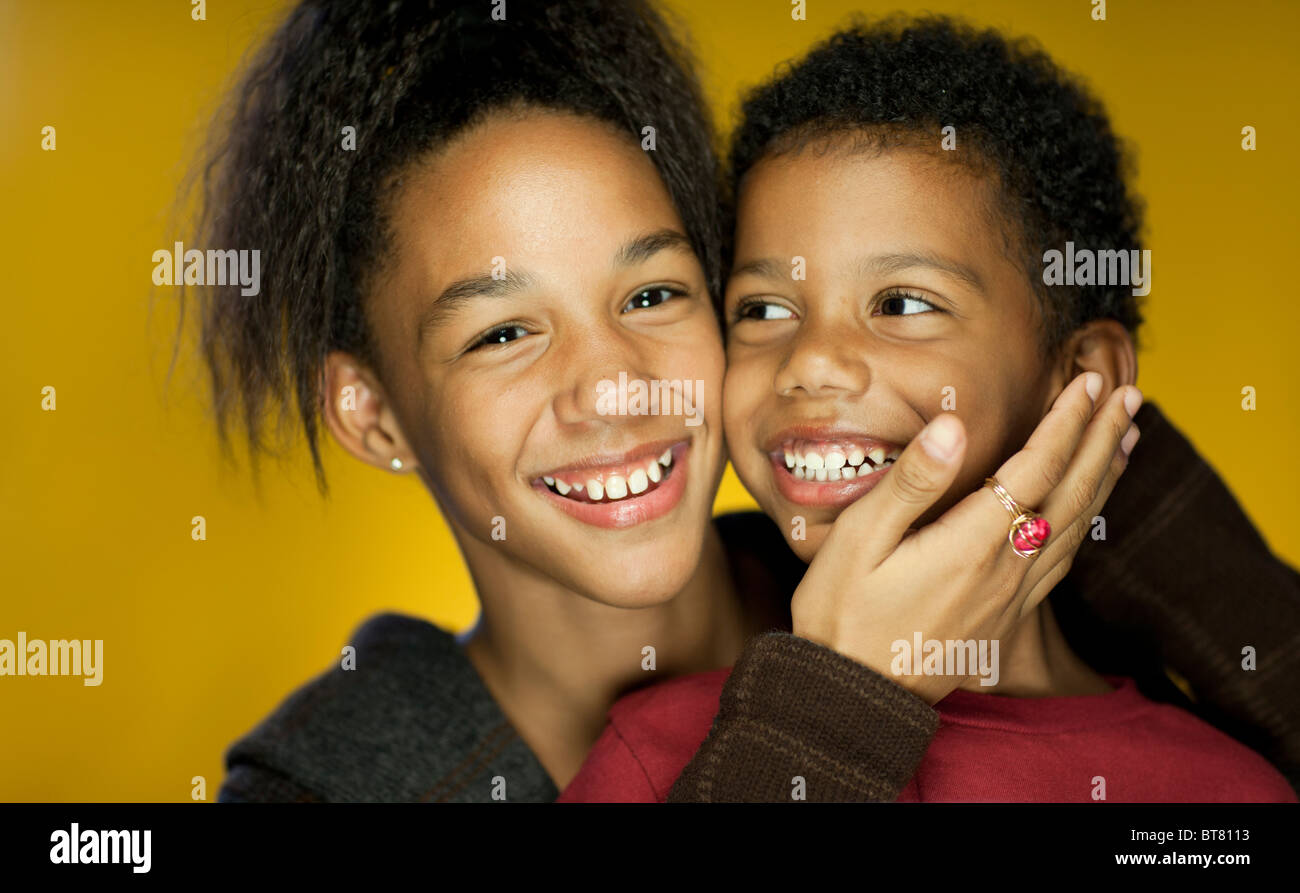 Portrait of a brother and sister smiling - Stock Image
