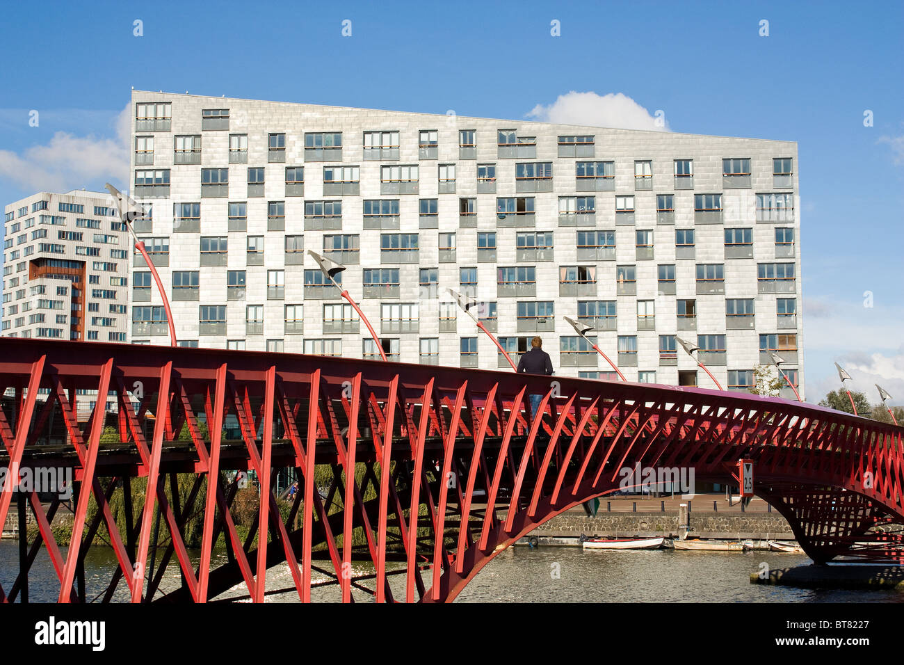 Modern architecture: Red steel bridge in  Amsterdam Eastern Docklands, Sfinx building in background, by  Frits van Stock Photo
