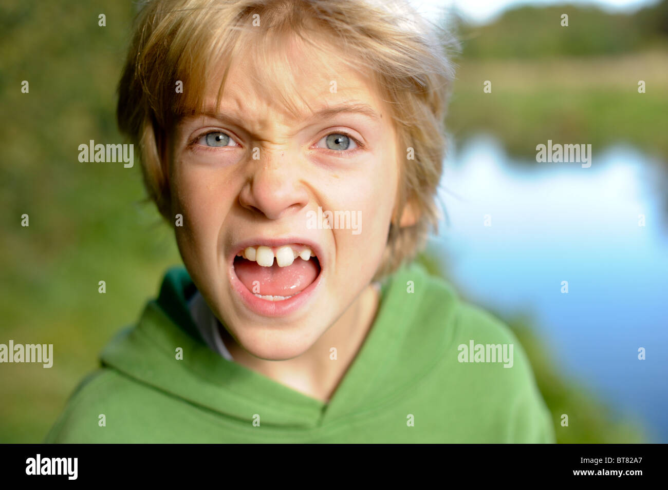 Animated young boy shouts and screams looking directly at the camera - Stock Image