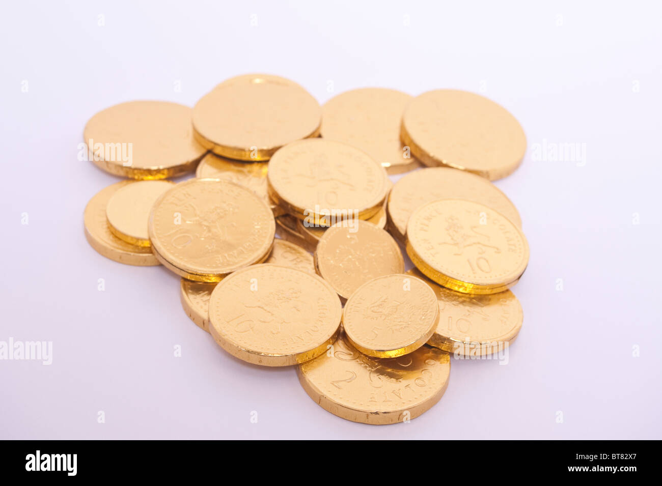 A close up photo of some gold chocolate coins against a white background - Stock Image