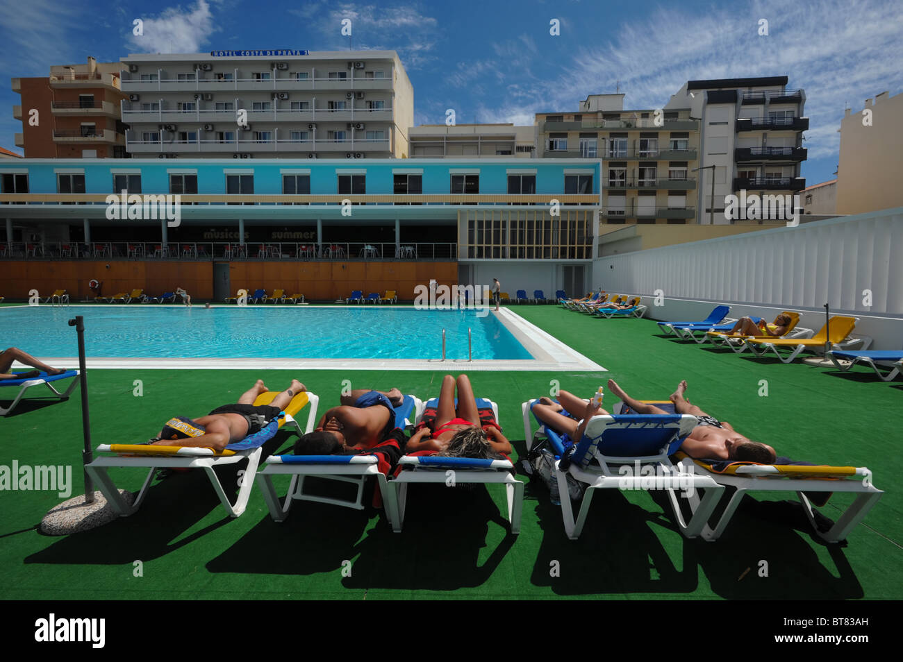 Group of people on lounge chairs sunbathing by a outdoor swimming pool Stock Photo