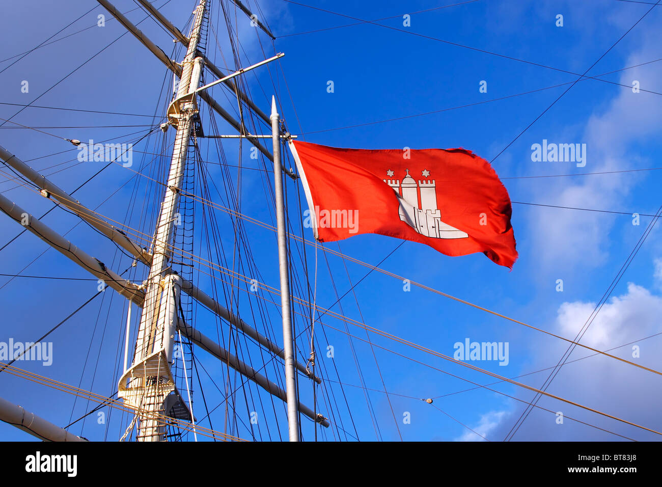Red flag of Hamburg in front of the mast and rigging of the historic sailing ship Rickmer Rickmers, museums ship - Stock Image